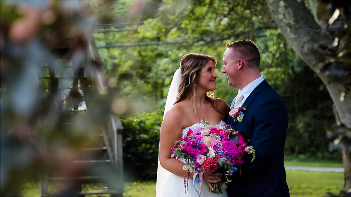 Couple posing for the camera with a colorful bouquet at Bittersweet Farm in Westport, Massachusetts