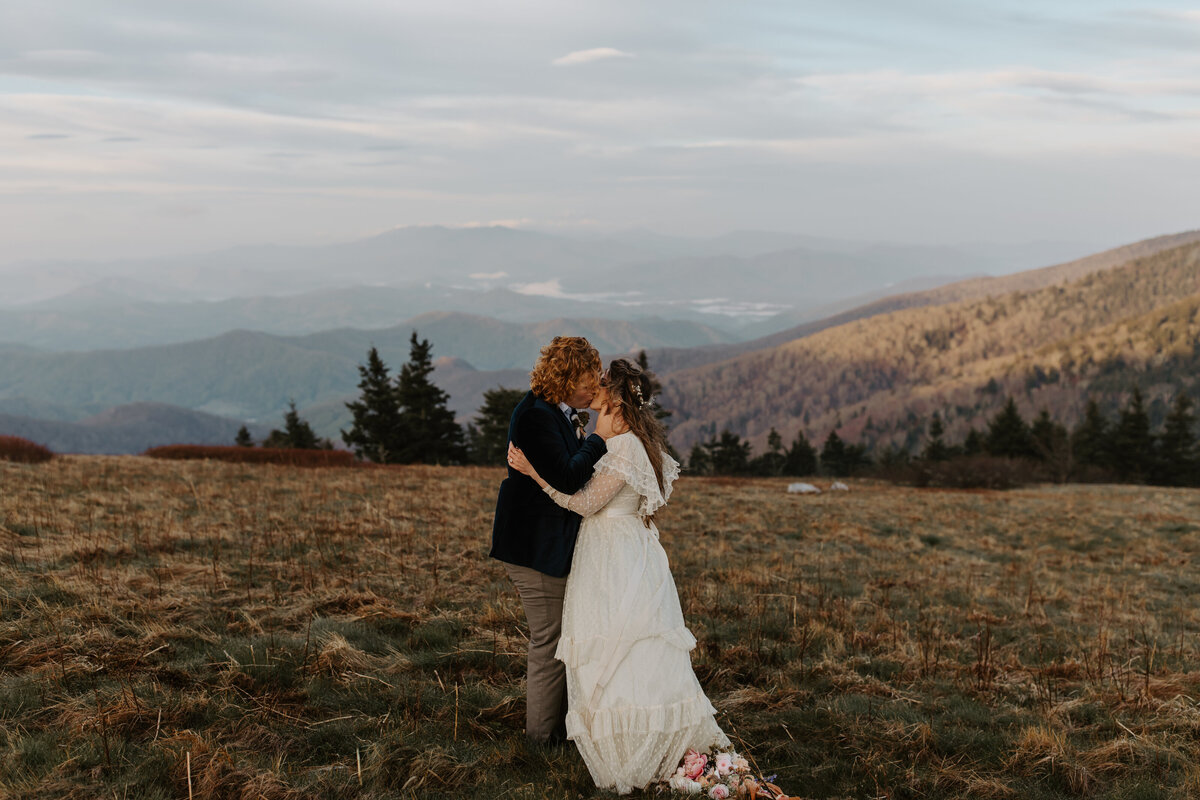 man and woman kissing on top of a mountain