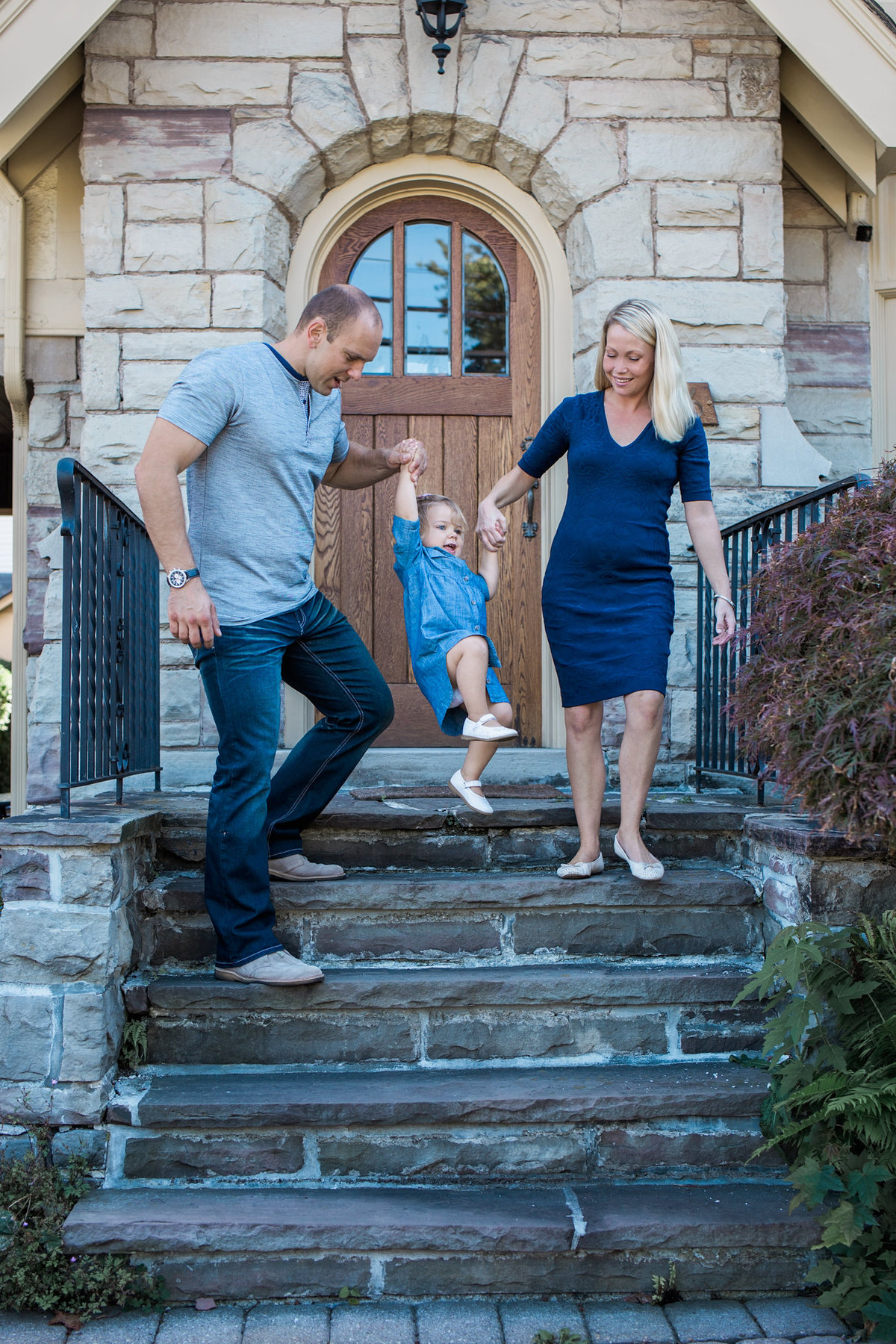 Family coming down front steps swinging daughter during lifestyle family session with Jennifer Blaak Photography
