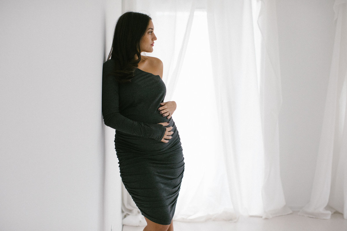 Natural pregnancy photo of a woman holding her belly in a black dress