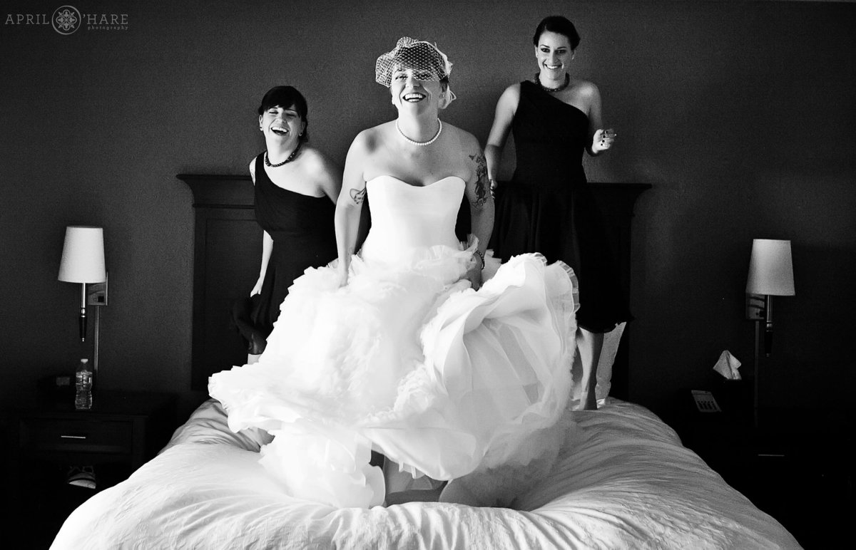 Silly Fun Photo of a Bride Jumping on her hotel bed in Denver Colorado in B&W