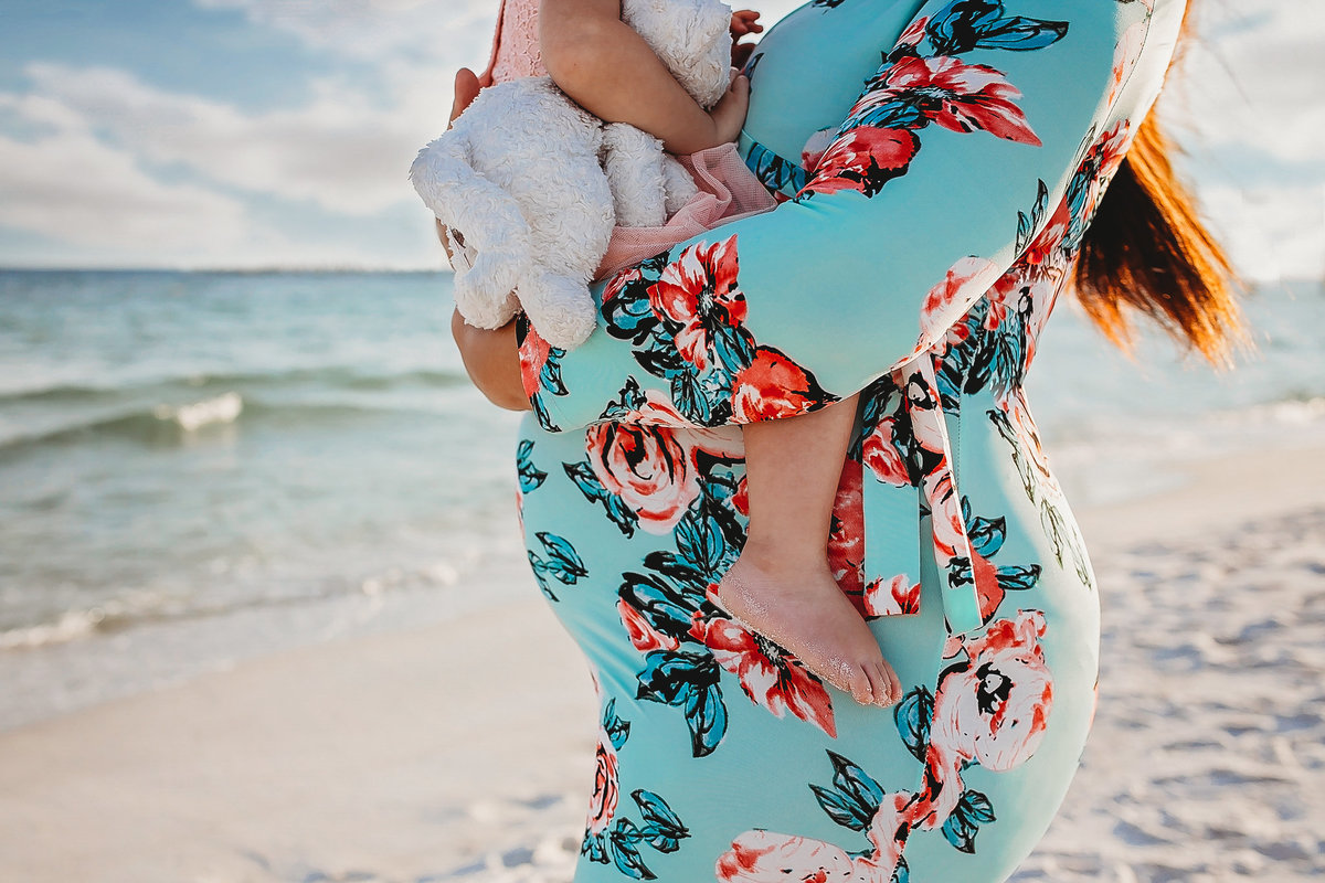 Mom and toddler daughter on beach, pregnant belly