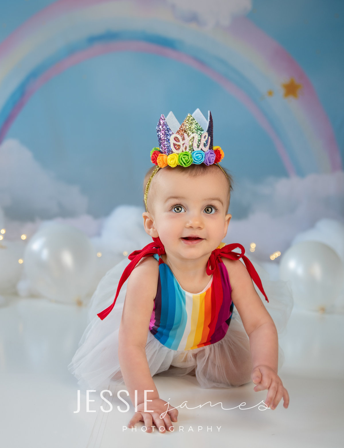 rainbow baby girl 1st birthday  posing in front of rainbow backdrop