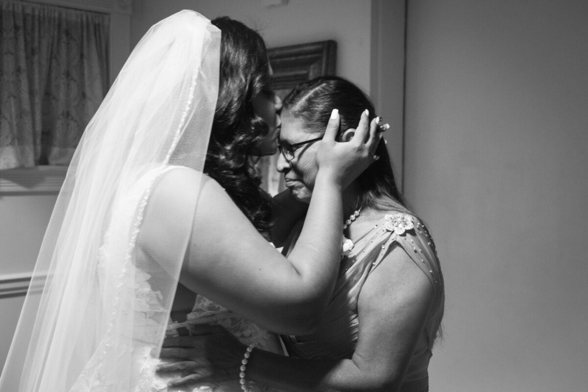 black and white image of bride kissing mothers forehead