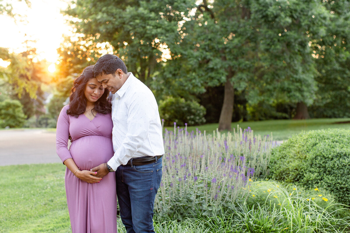 Spring Sunset Maternity Session with pink maxi dress standing by lavender  at Oak Knoll Park in St. Louis by Amy Britton Photography Photographer  in St. Louis