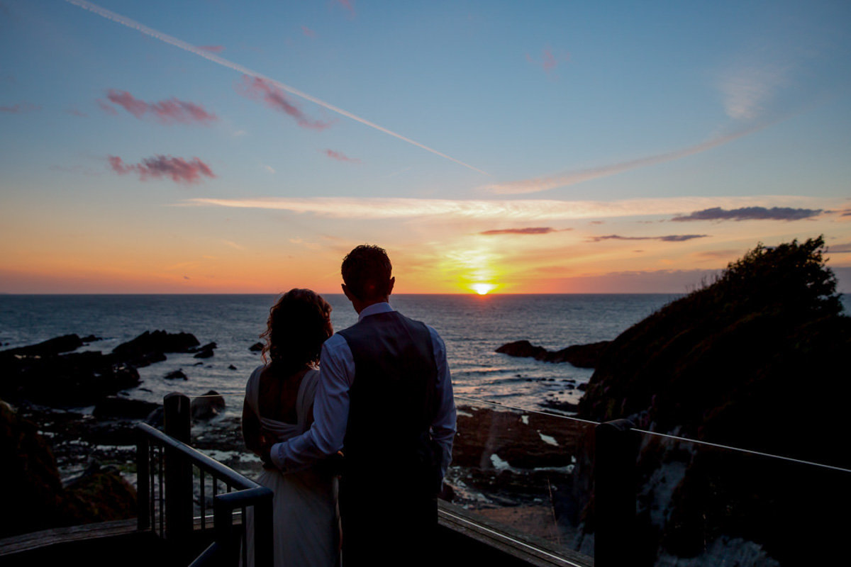 Married couple watching Sunset at Tunnels Beaches Wedding in Devon