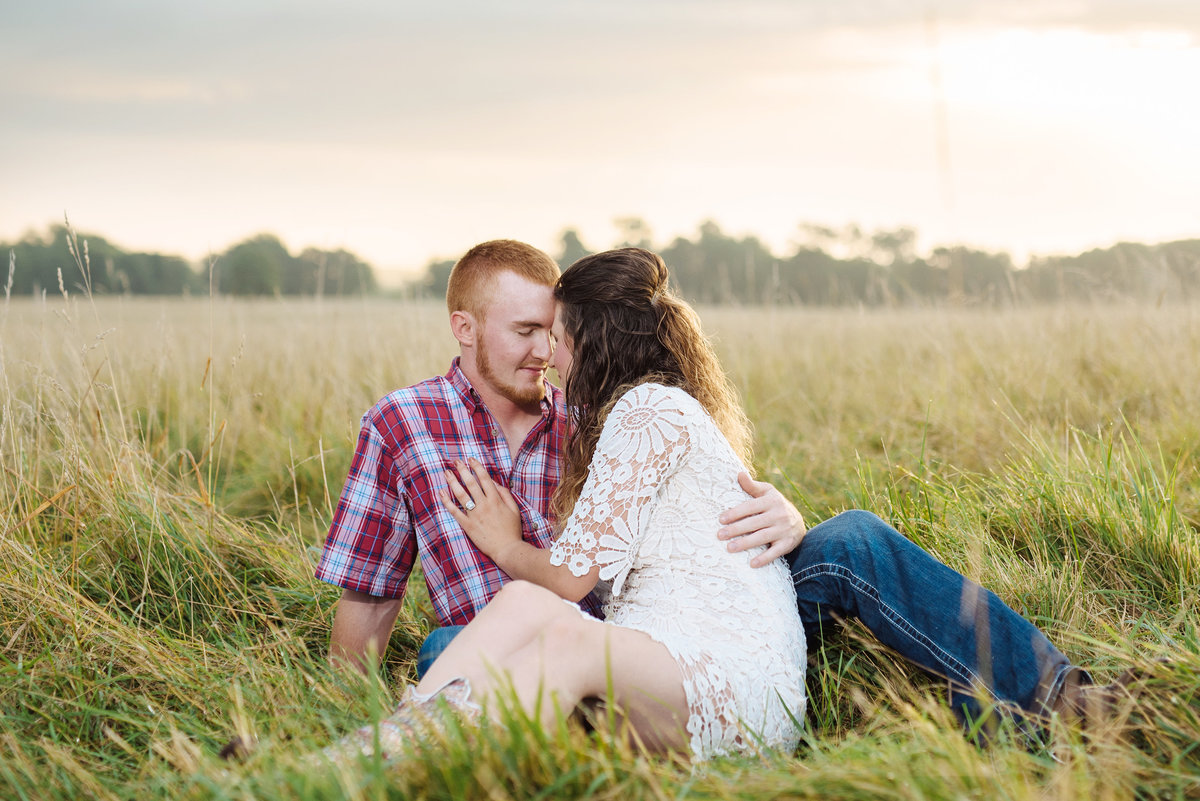 engaged couple snuggles in a field at sunrise