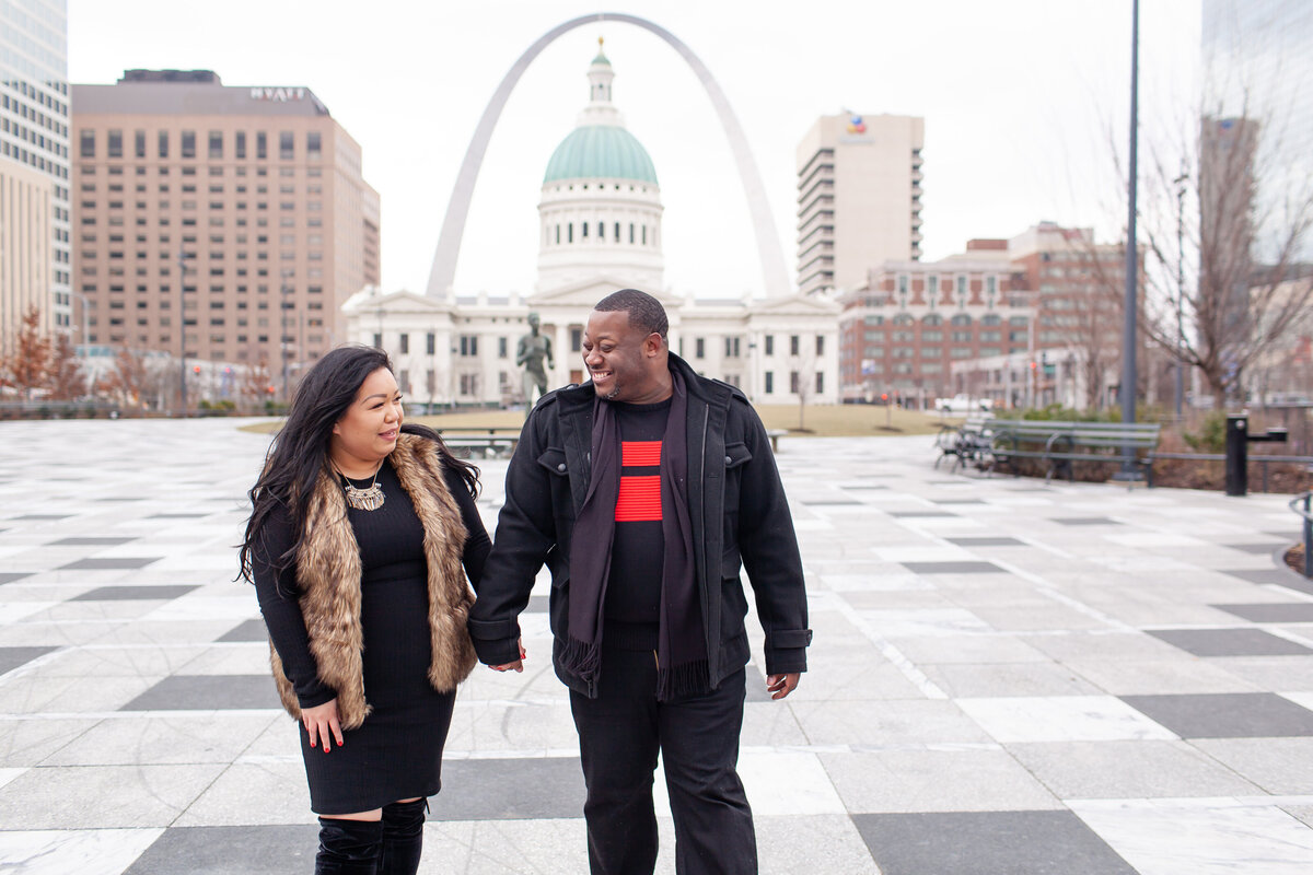 Winter Engagement  Session with black dress fur vest and boots couple holding hands walking in front of The St. Louis Arch  at Kiener Plaza in St. Louis by Amy Britton Photography Photographer in St. Louis