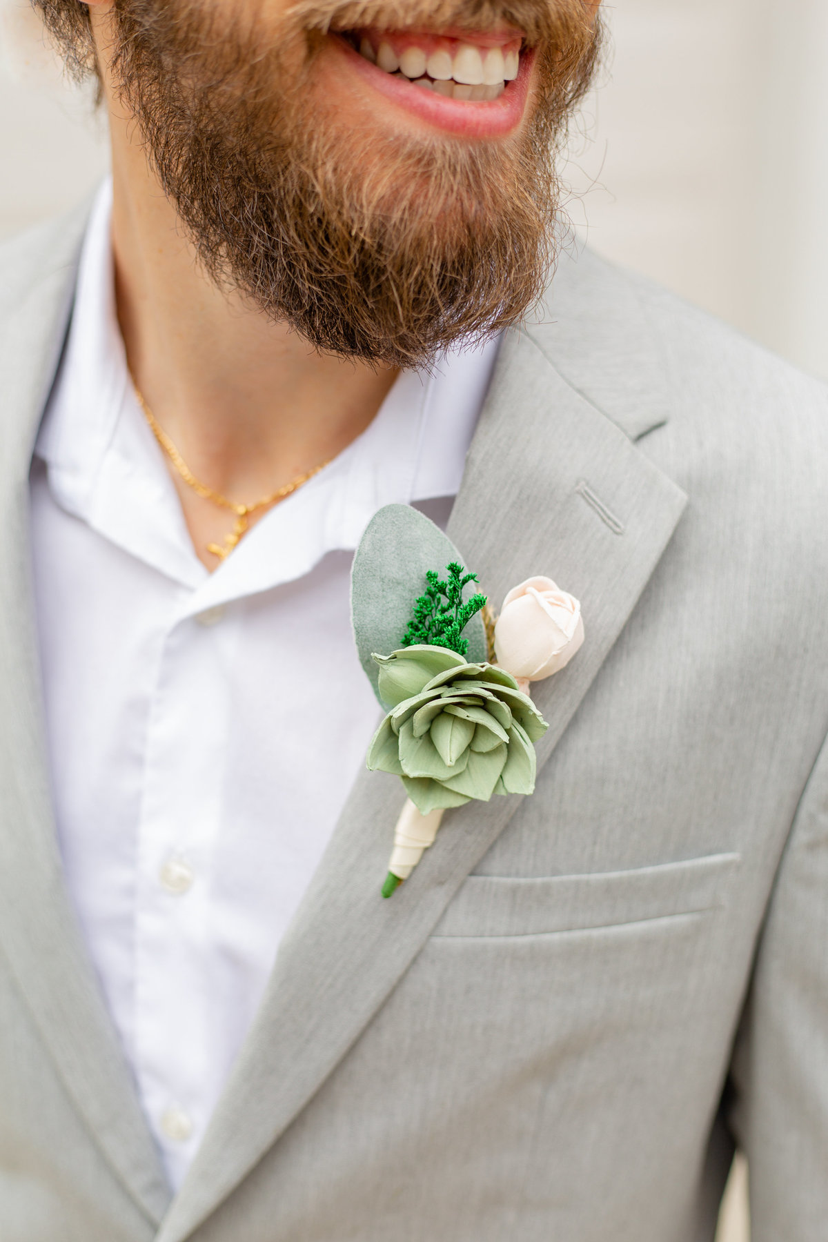 Groom with beard smiles off camera on his wedding day in his grey suit and white dress shirt with his green and white boutonniere