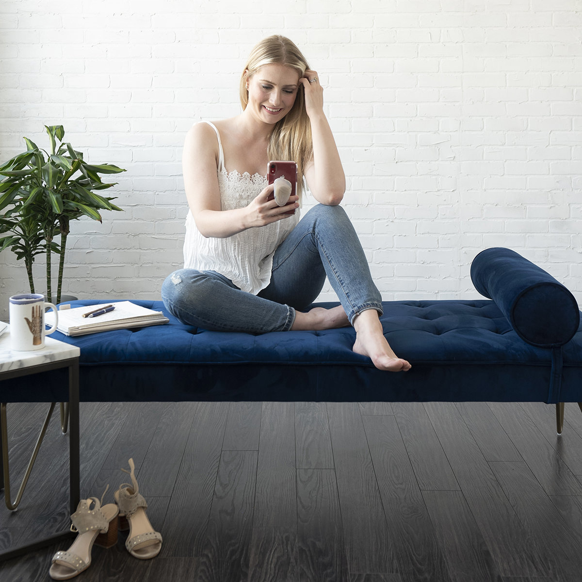 woman sitting on couch looking at her phone
