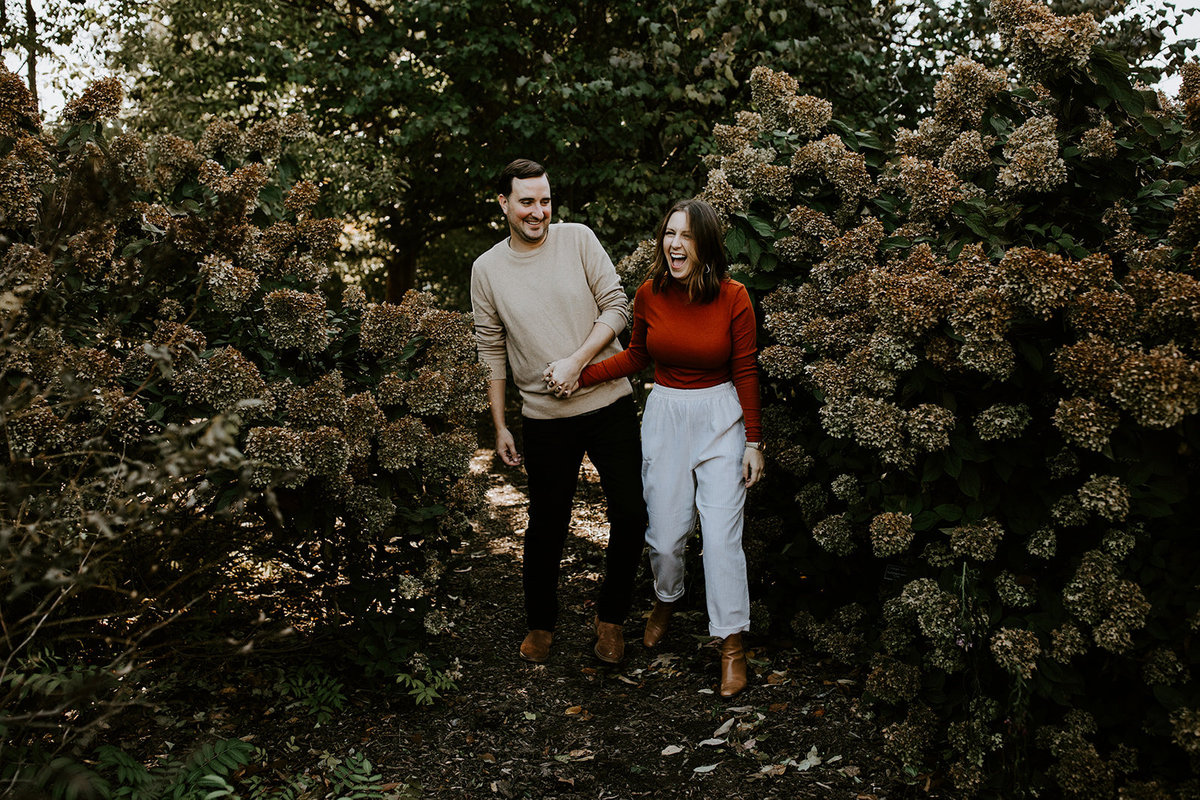 A man and woman holding hands walking through bushes.