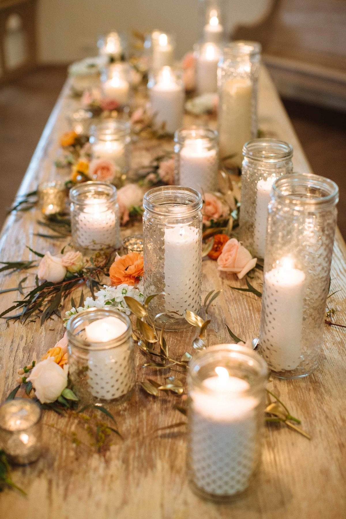 A table decorated for a wedding reception with lots of candles.