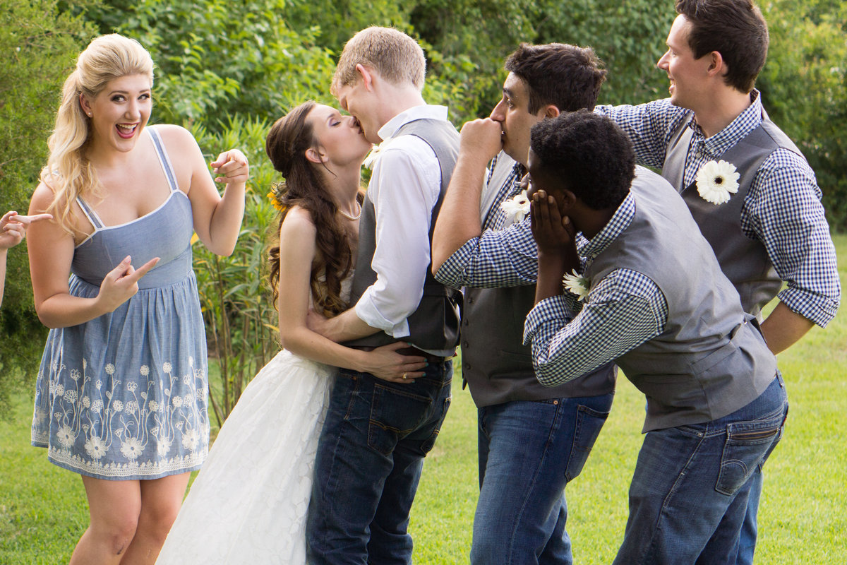 Bride & Groom kissing with bridal party snickering