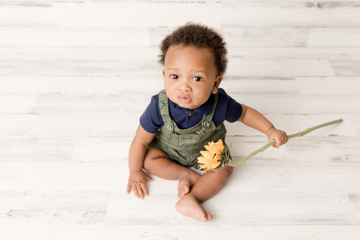 baby boy grips yellow sunflower during photo session