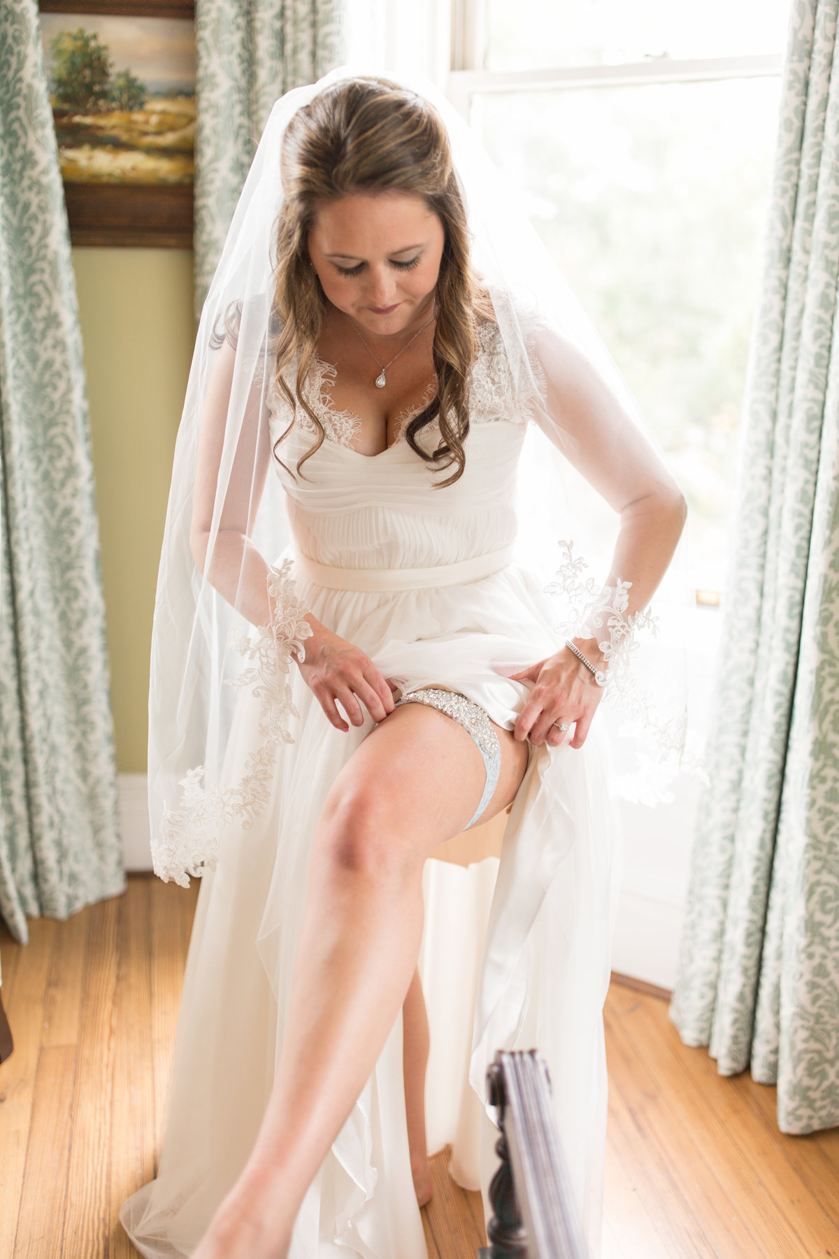 bride putting on ehr garter at the kehoe house in savannah before her destination wedding