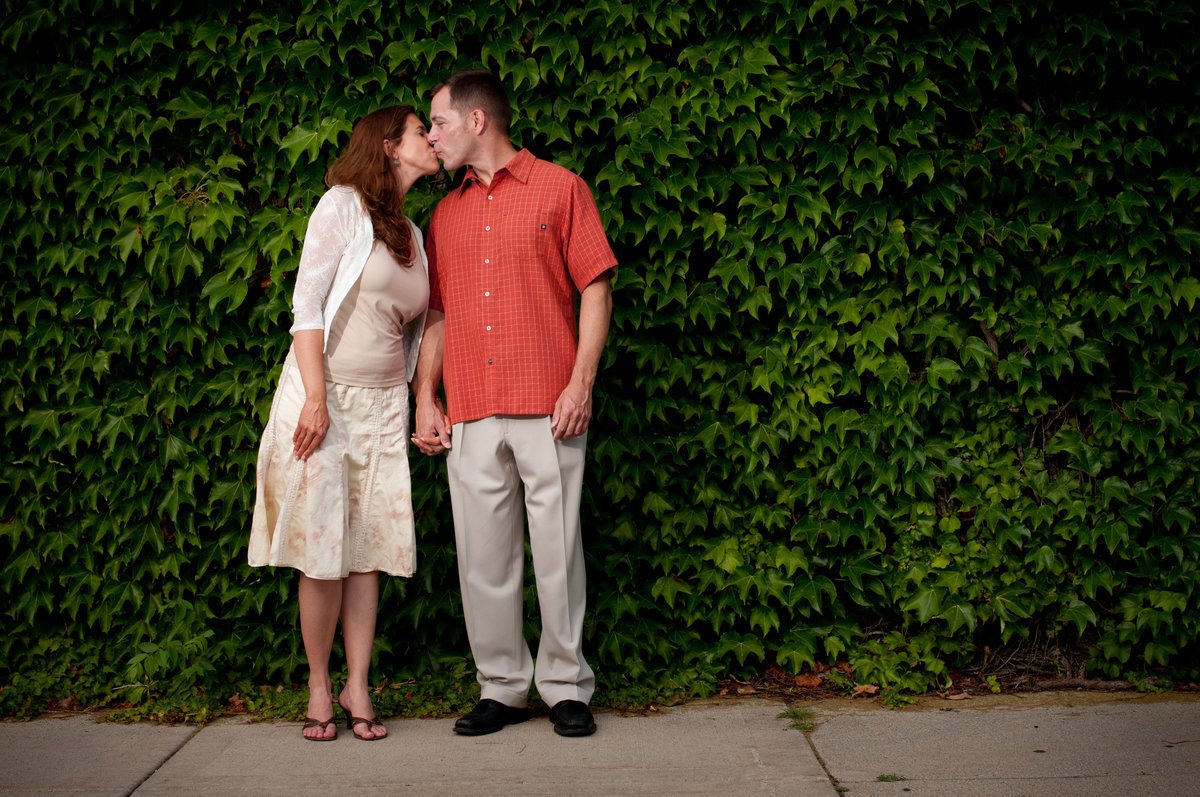 Kissing couple against an ivy covered brick wall