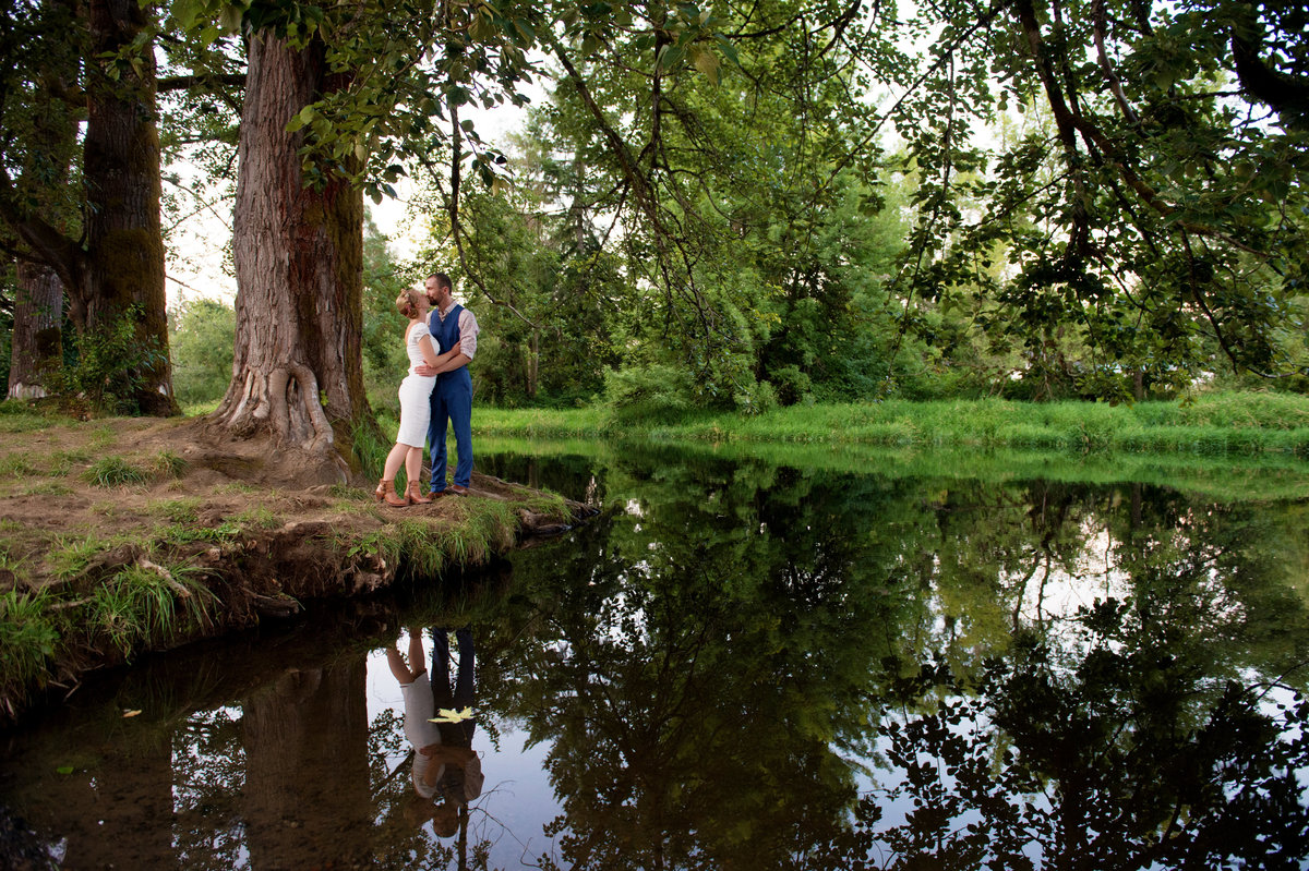 bride and groom kiss by river in vernonia or