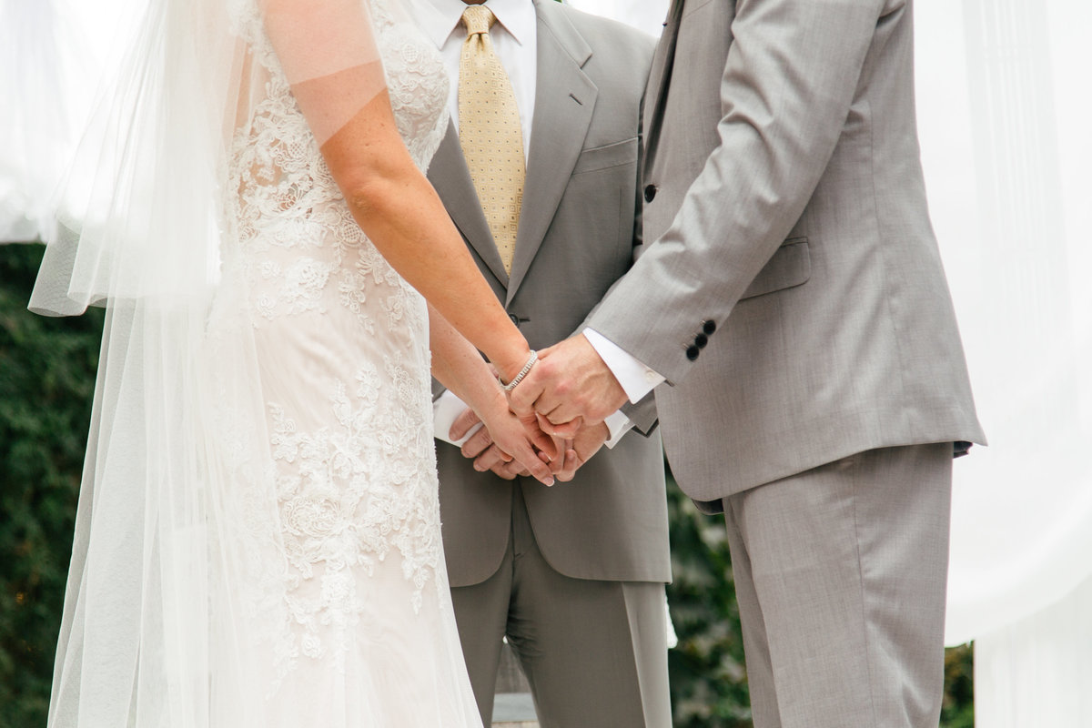 Bride and groom hold hands at 1880 Union Hotel Wedding