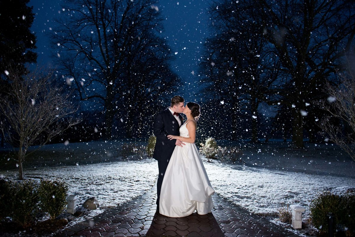 Bride and groom kissing outside during a snow shower at The Mansion at Oyster Bay