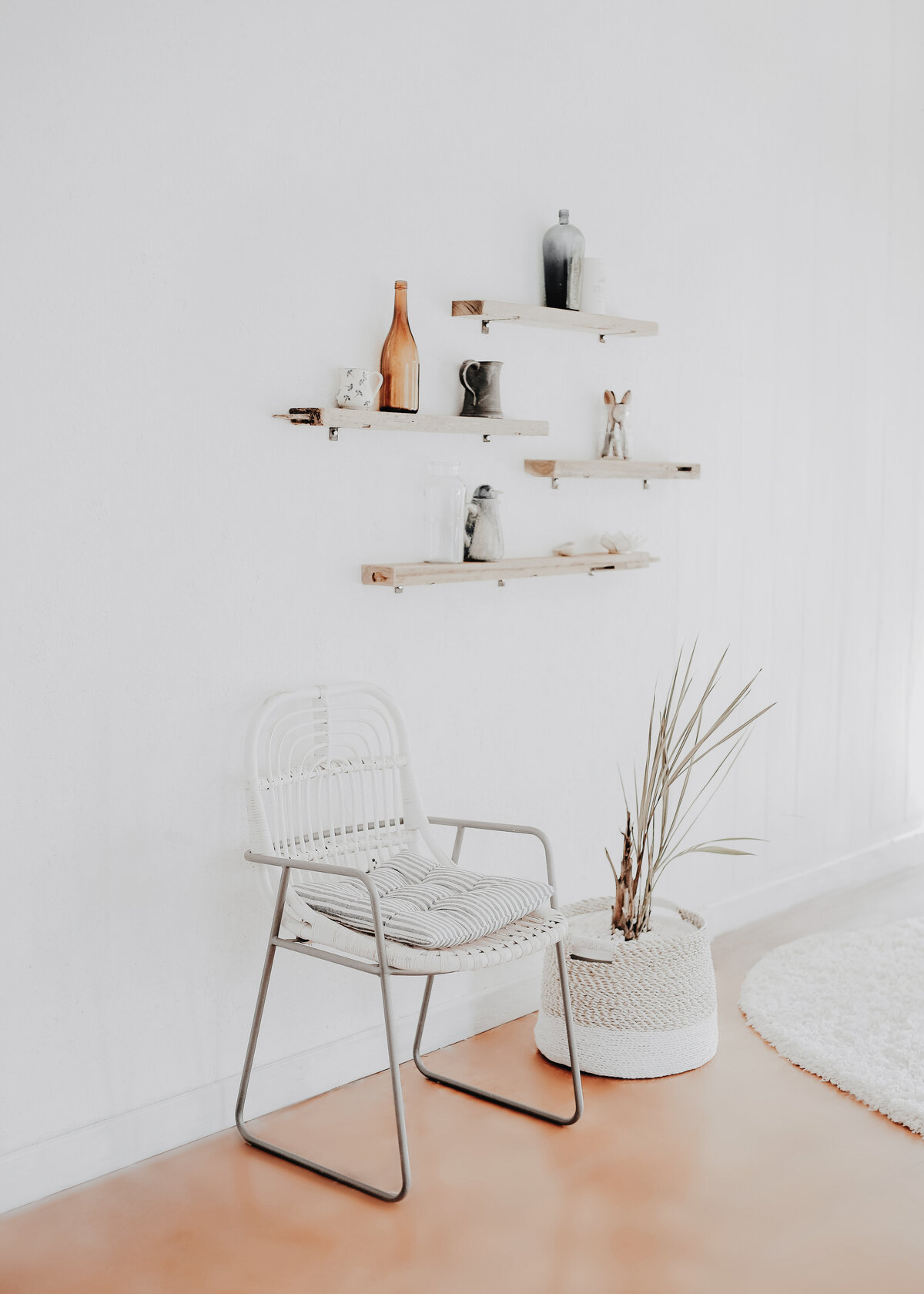 A minimal white decor with wooden shelves and a white rattan chair with a palm in a white basket.