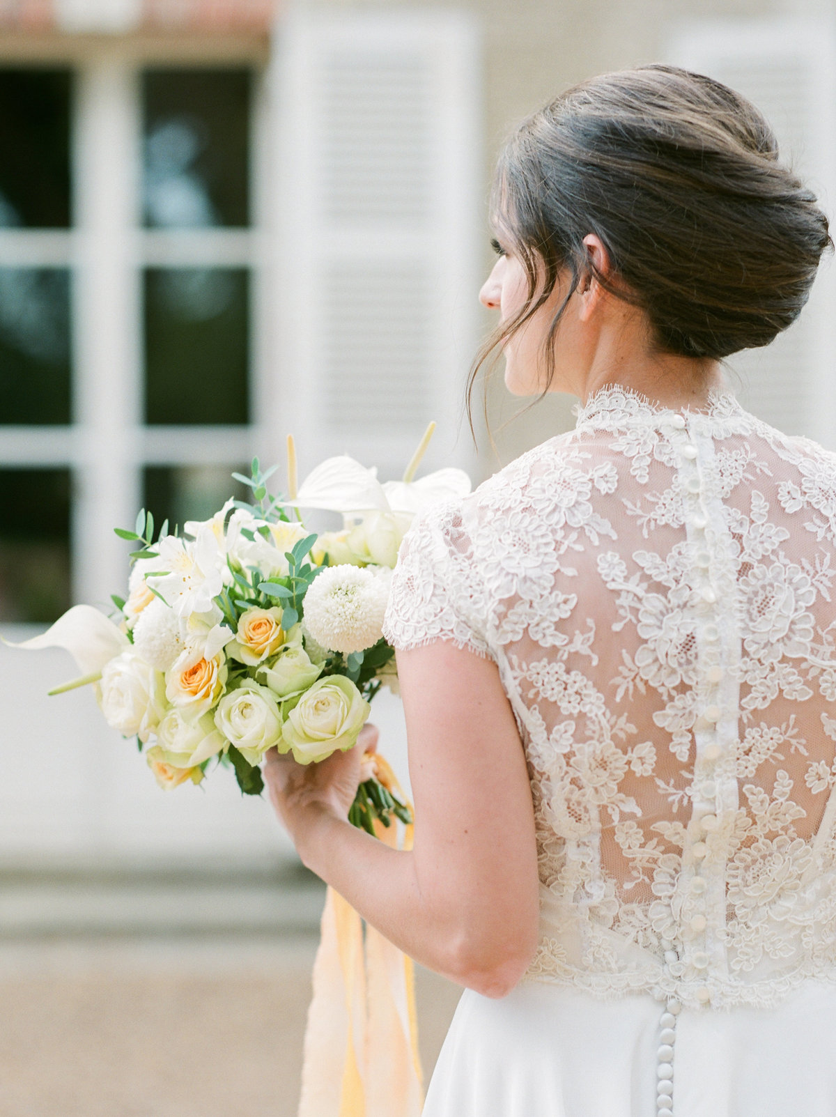 bride in short sleeve lace dress holding bouquet looking away from camera