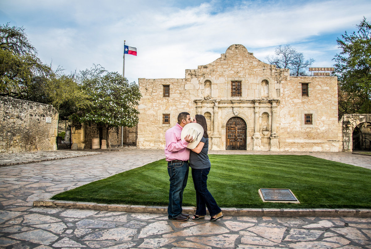 Fiancé and fiancée standing in front of the Alamo in San Antonio hiding their kiss behind a cowboy hat.