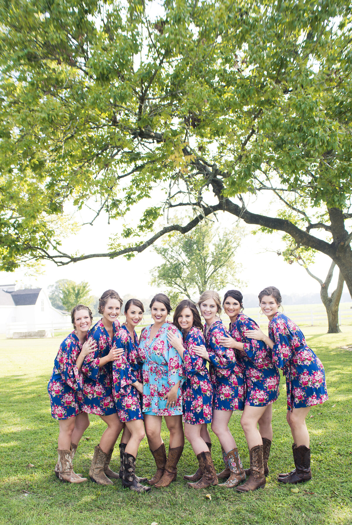 A gorgeous bridal party standing together in floral robes and cowgirl boots for a photo op