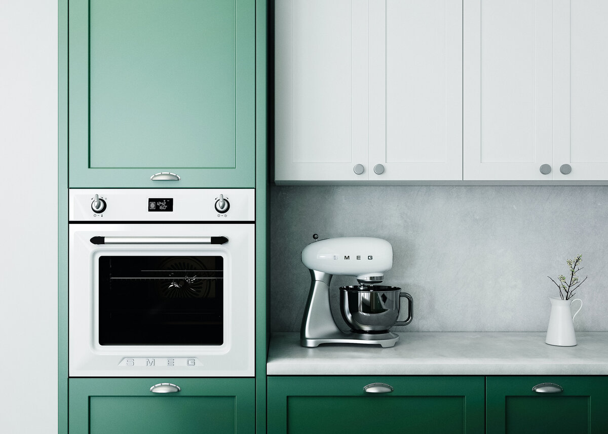 A close up image of a modern forest green kitchen with smeg appliances and a marble backsplash.