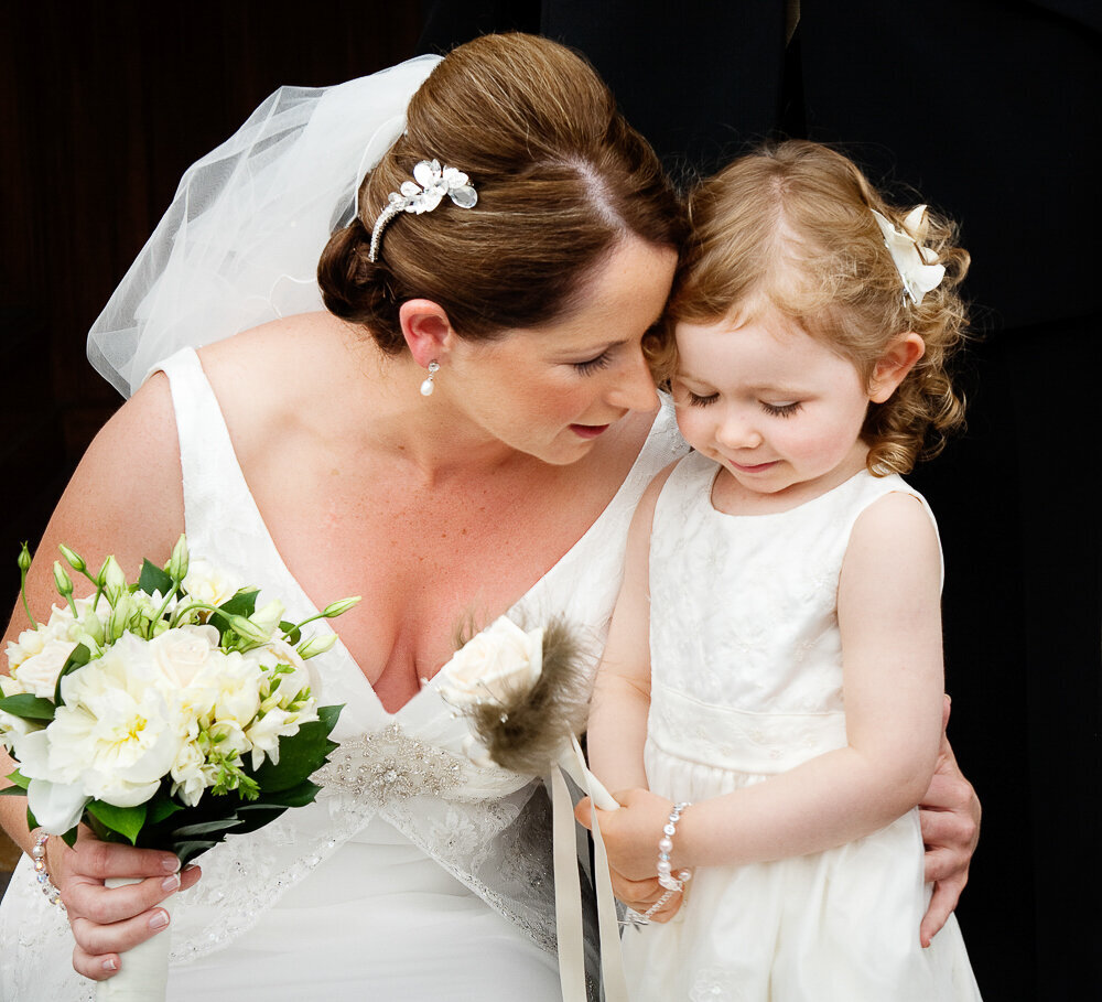 bride wearing a v neck wedding dress and hair piece hugging small flower girl