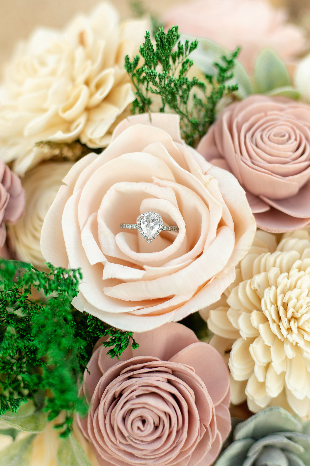 Pear shaped engagement ring close up in blush and cream wooden flower arrangement in Davenport, Florida