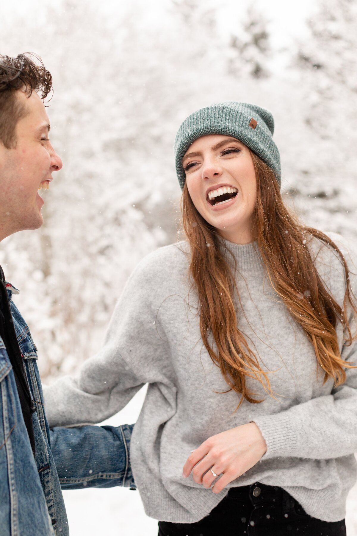 Casual-and-fashionable-couple-laughs-after-a-snow-fight-during-their-winter-engagement-session-at-Sydenham-ridge
