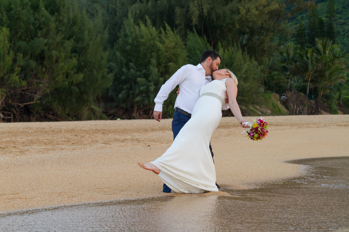 Groom dips bride by the water at Kauai beach wedding.