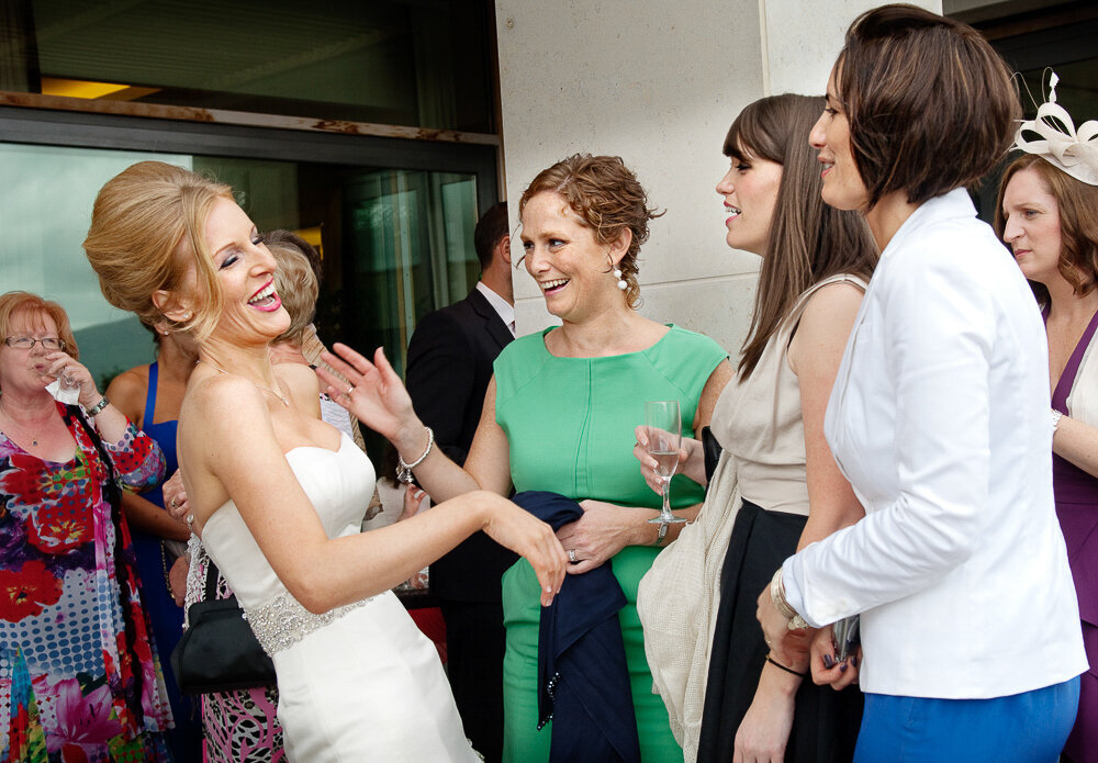 bride with beehive hairstyle wearing a trumpet style wedding dress laughing with her friends at the Europe Hotel, Killarney