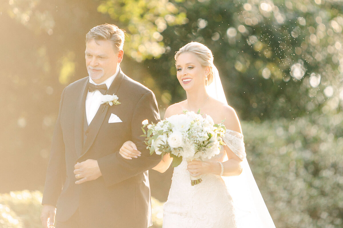 Father and Bride walking in green garden to Dallas Arboretum wedding ceremony altar smiling