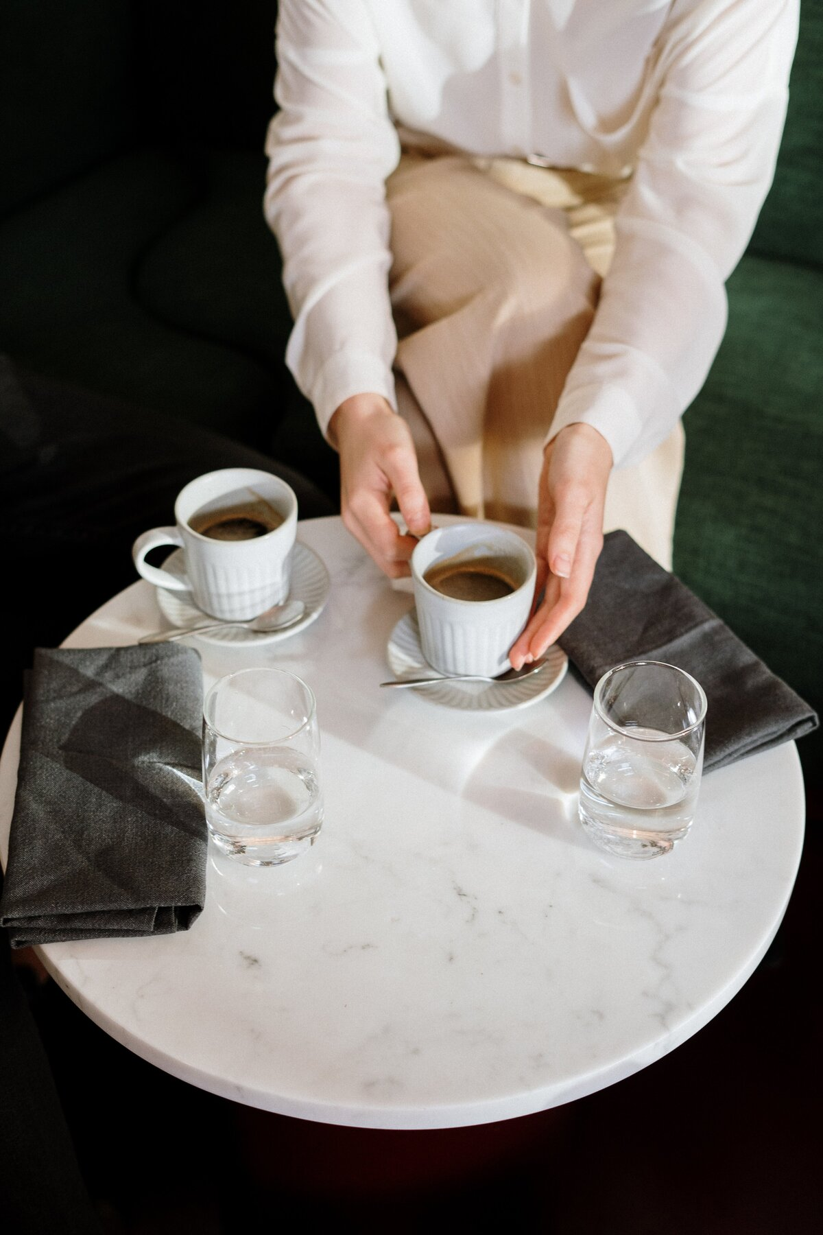 person-holding-white-ceramic-cup-on-white-table-4255416