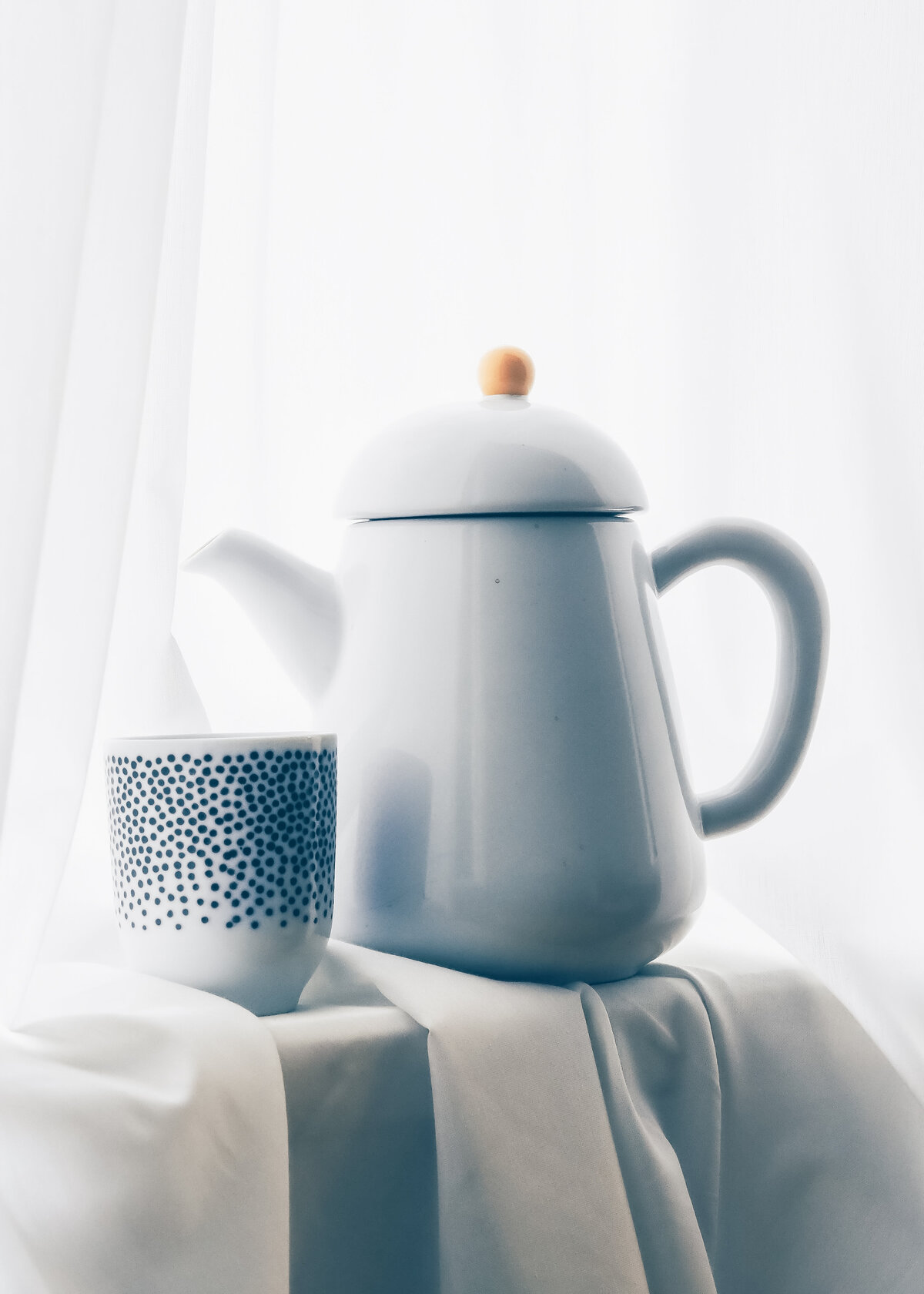 A glossy porcelain teapot is poctured with a dappled blue mug. Interior accent.