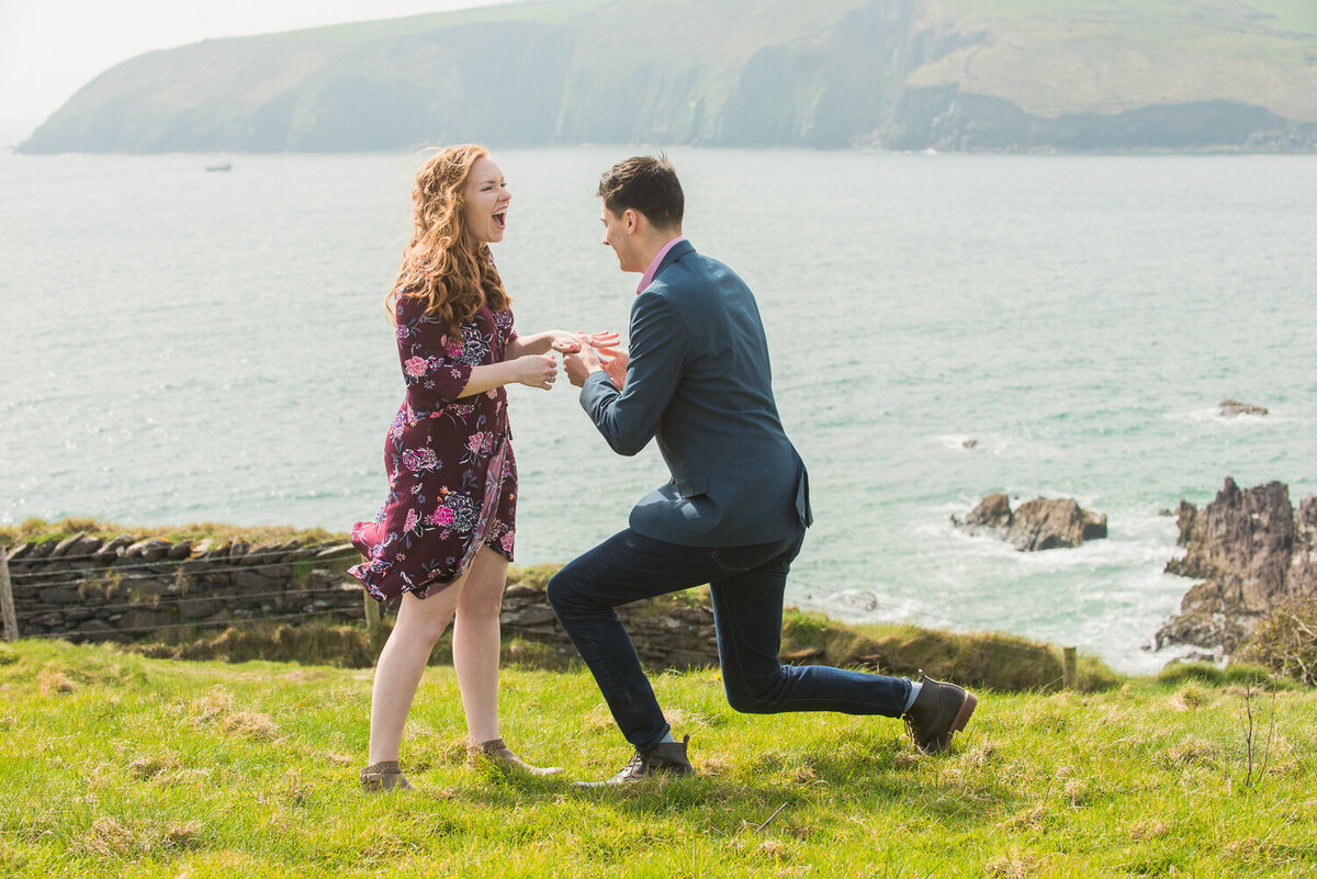 Romantic portrait of a young man proposing to his girlfriend in a field overlooking the sea