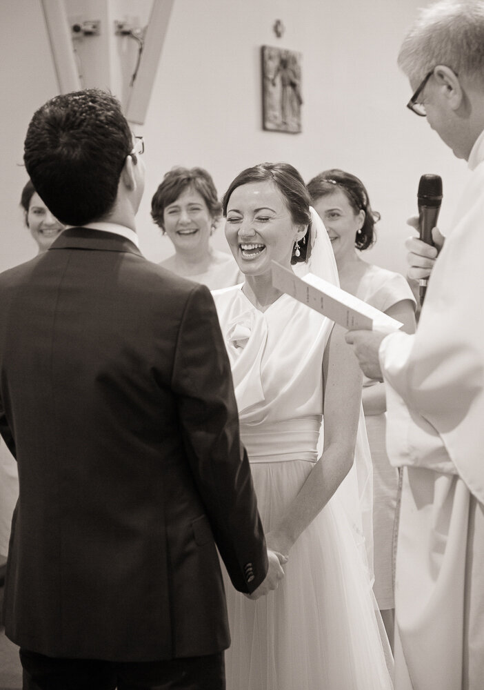 bride wearing a tulle and satin a-line wedding dress laughing while exchanging vows with her groom in Curaheen church