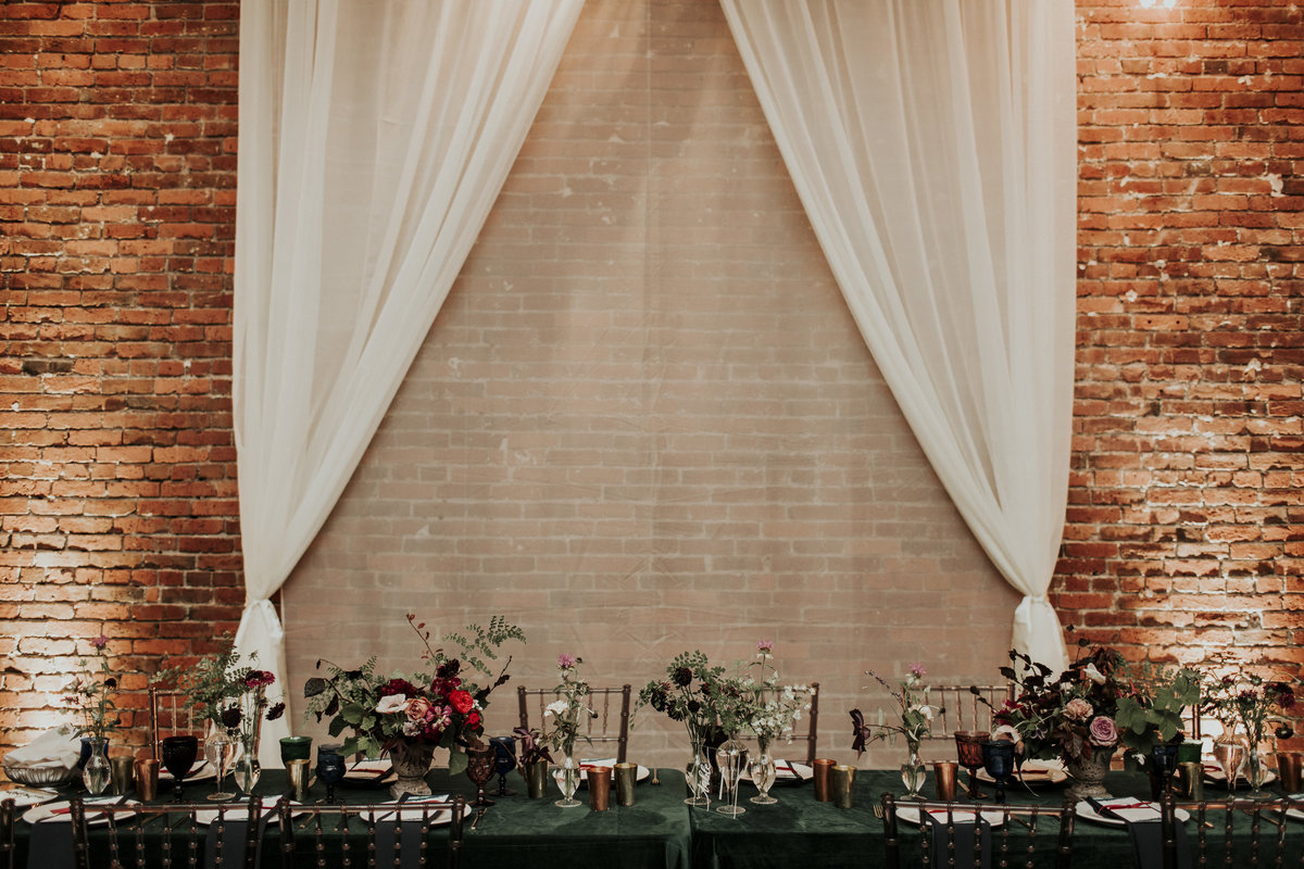 Jewel tone wedding reception with green velvet table cloths