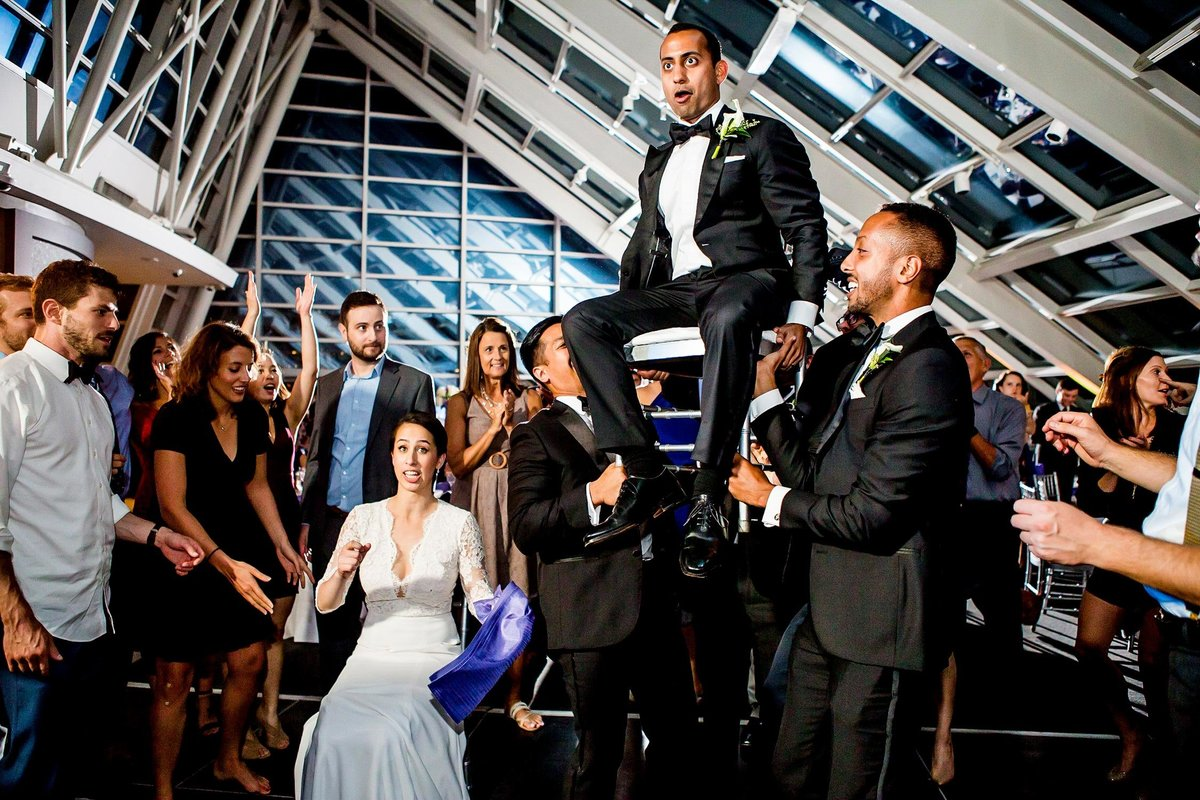The bride and groom are hoisted in chairs for the Hora at an Adler Planetarium wedding.