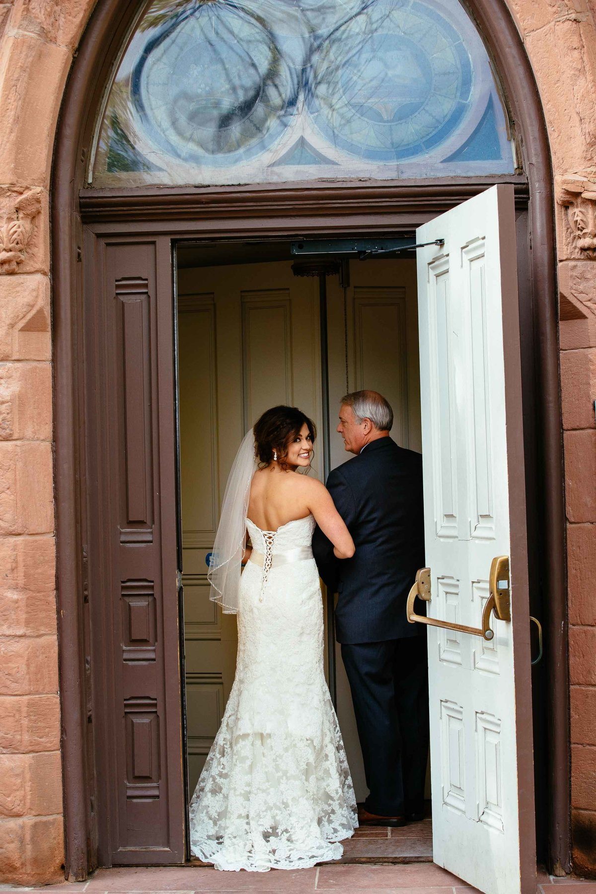 A bride walking into a church holding her father's hand.