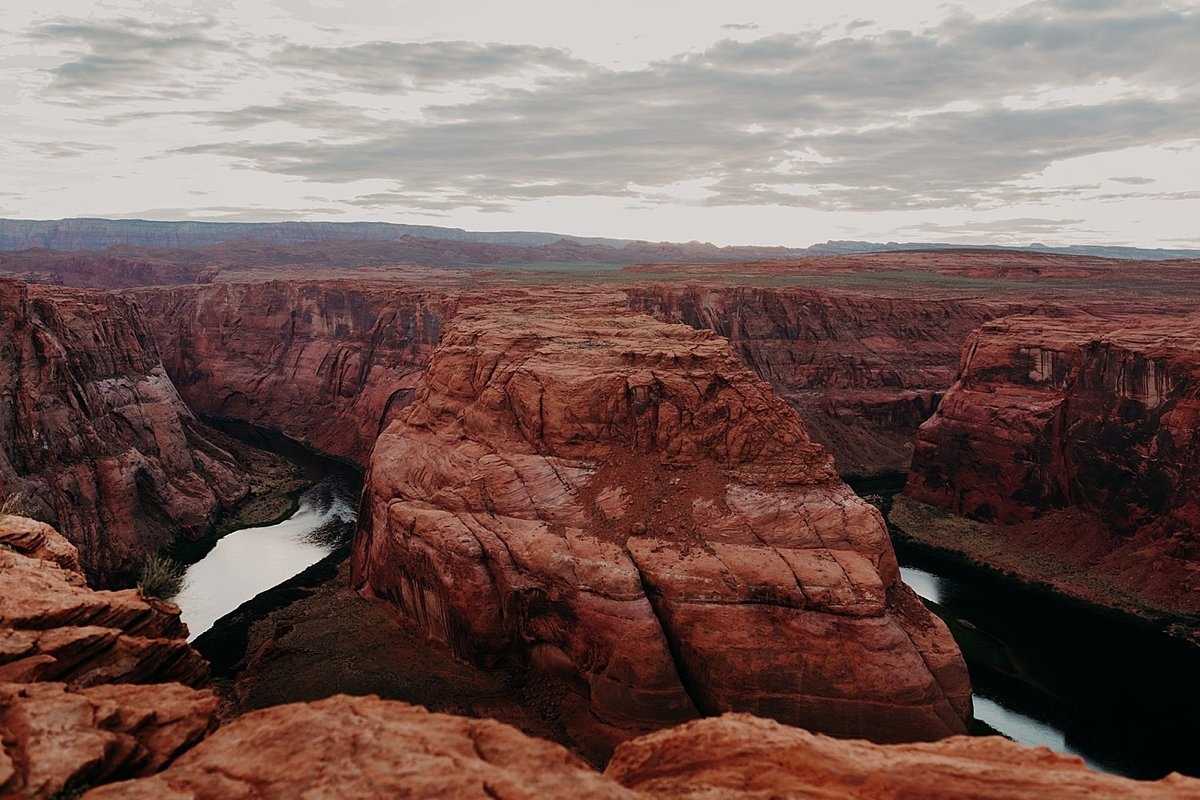 photo of horseshoe bend where the colorado river cuts through the red rocks like a curved horseshoe