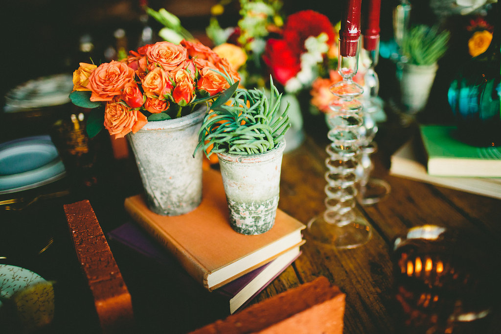 Mixed floral arrangements with potted plants and orange flowers for dinner party
