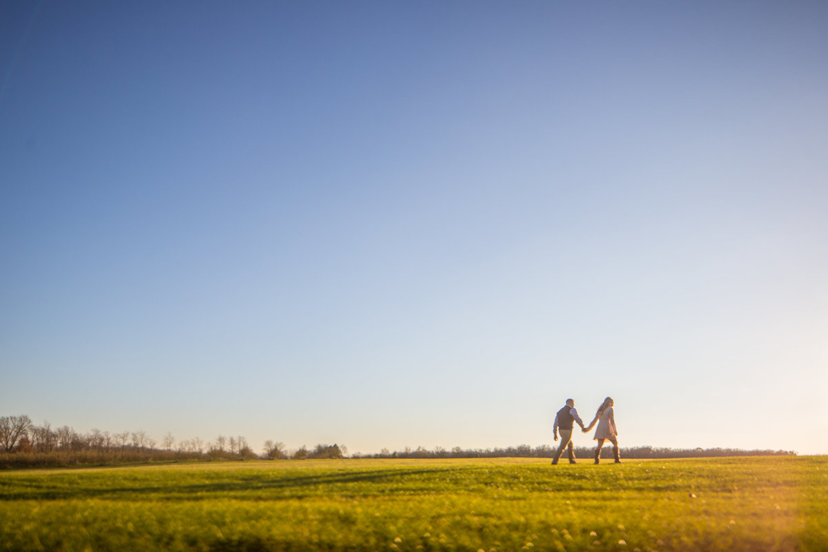 couple walking at sunset during their engagement photographs