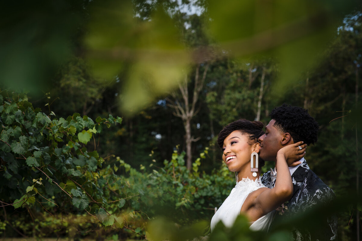 Black bride and groom smiling outdoors
