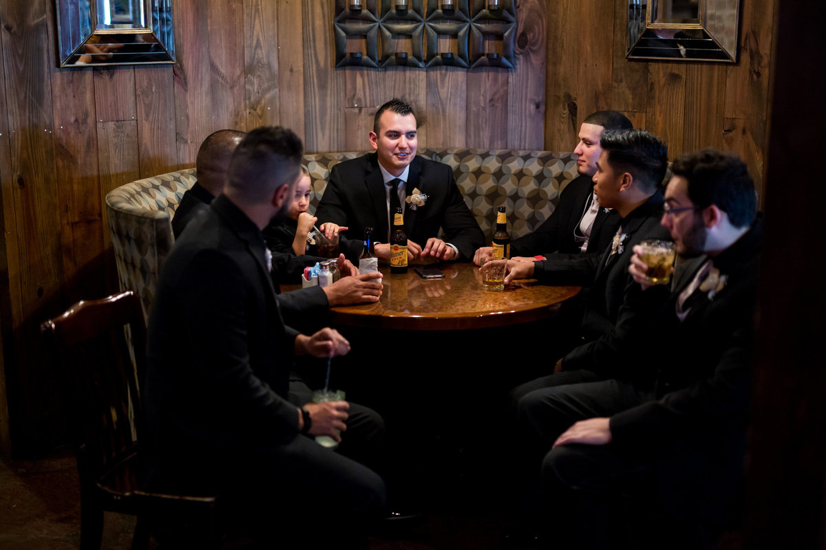 groom and groomsmen have a drink before wedding ceremony in Texas Hill Country wedding