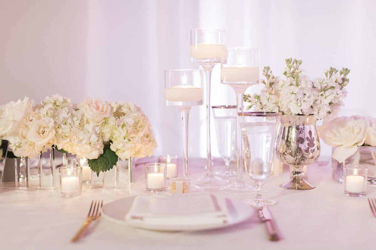 Soft and romantic all white reception with hydrangea, roses and stock, plus an abundance of candles!