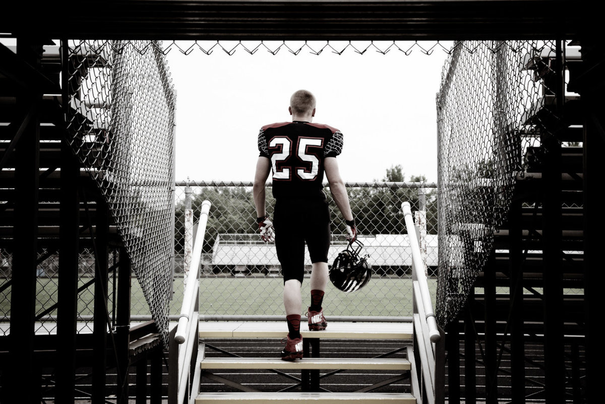 sioux falls senior photography football player on stairs at field