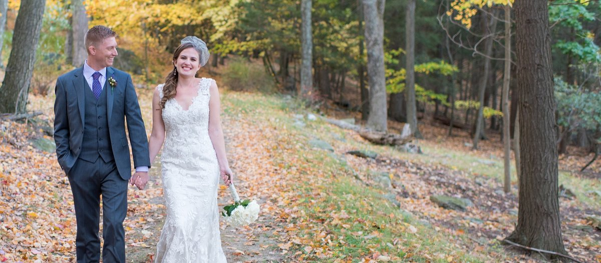 Bride and Groom Laughing while Walking through a Forest during the Fall at Sedgewood Country Club in Carmel, New York Photo