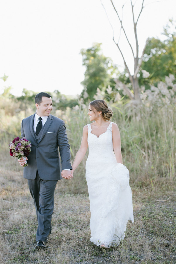 casual wedding photograph of bride and groom walking
